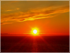 初夏の広大な海が真っ赤に染まる夕陽